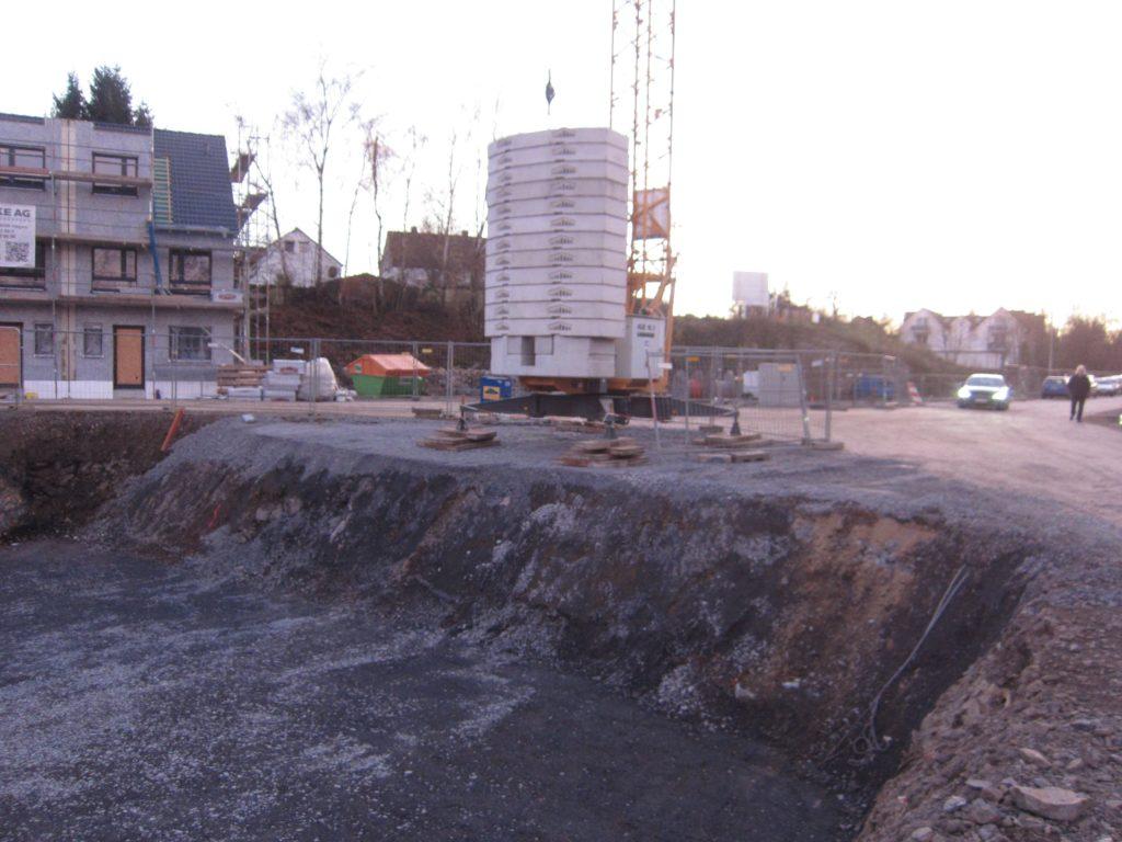 Der Kran am Abgrund der Baugrube auf frisch Aufgeschottertem - ob das standsicher ist?